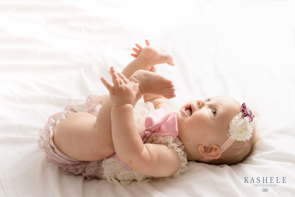 Little girl in lace romper grabbing her toes during milestone session