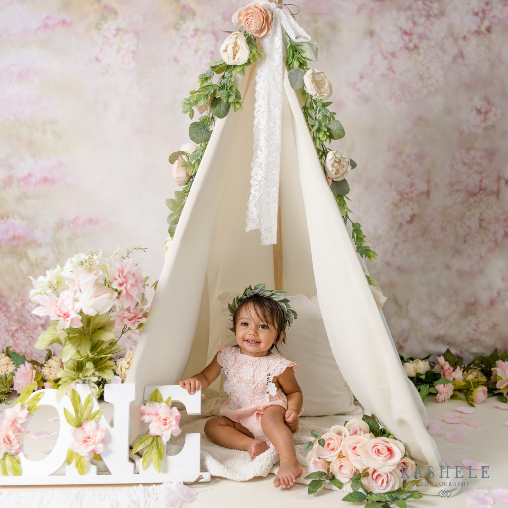 One year old sitting in a teepee for her milestone cake smash session
