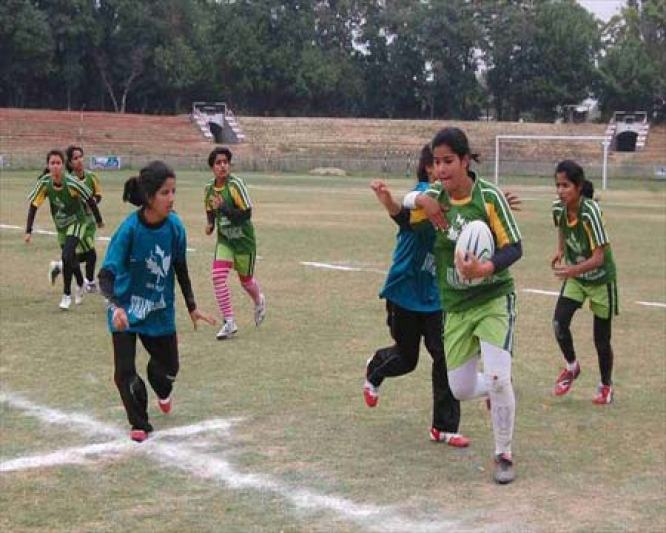 Girls playing Rugby at the outdated Bakshi Stadium in Srinagar