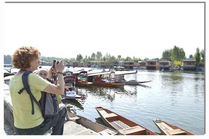 A foreign toursist taking snap in Dal Lake -- Photo: Bilal Bahadur