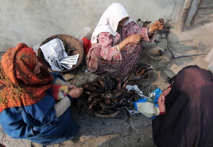 Finally women dressed in traditional attire sell smoked fishes on roadsides in many places of Srinagar.