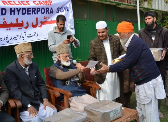 Senior Hurriyat leader Syed Ali Geelani distributing relief among flood-hit.