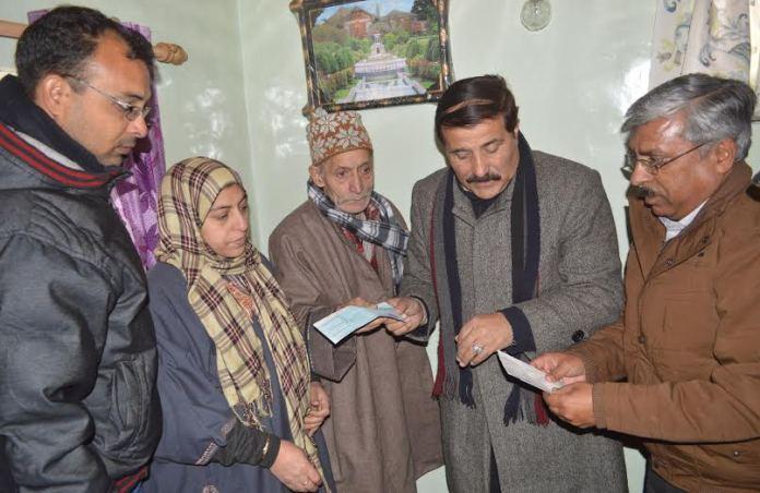 MLA Eidgah Mubarak Gul handing over Ex-Gratia relief cheque to late Shafat Siddiqui's family in Srinagar.