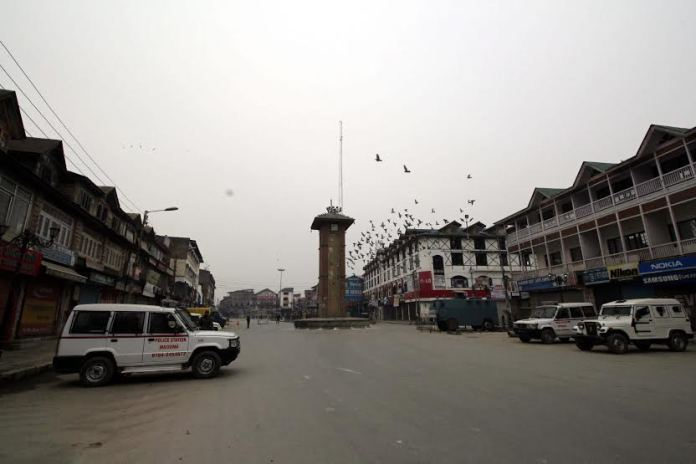 Policemen stand guard infront of closed shops during Strike in Srinagar on Tuesday 26, January 2015.  KL Image By: BILAL BAHADUR