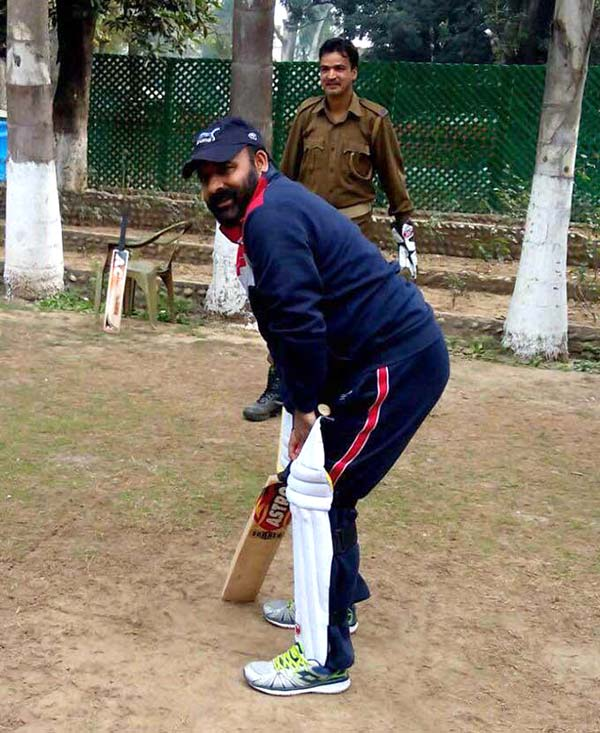 Killing Time: Former BJP minister Bali Baghat playing cricket with cops at his official residence in Jammu.