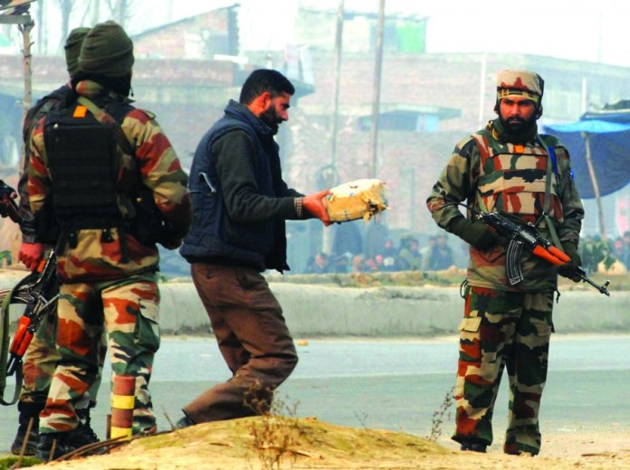 A bomb disposal squad man carrying the IED for diffusing in Narbal on the outskirts of Srinagar on November 21, 2015. Army and paramilitary troopers claimed to have recovered an IED near the Srinagar-Muzaffarabad road. PHOTO BY BILAL BAHADUR