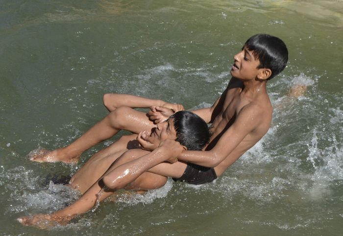 Boys swim in a river as mercury rises in the Valley