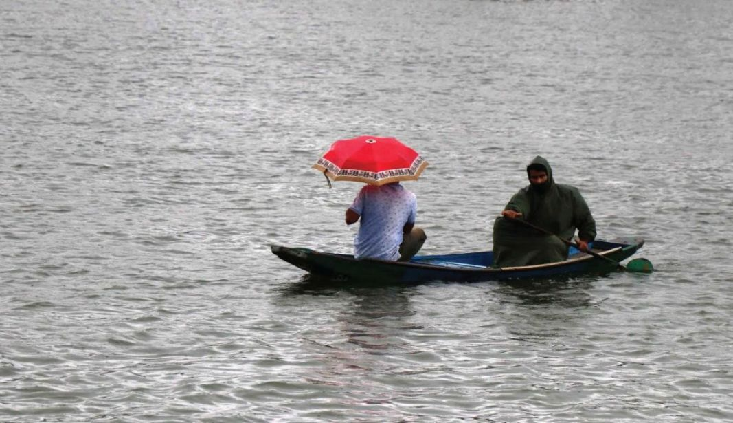 A man rowing Shikara amid rains in Dal Lake