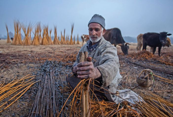 A craftsman peels wicker at Ganderbal for making Kangris