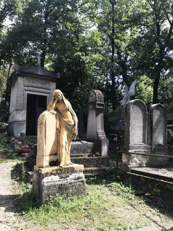 yellow statue of a woman leaning on a lyre in a cemetery