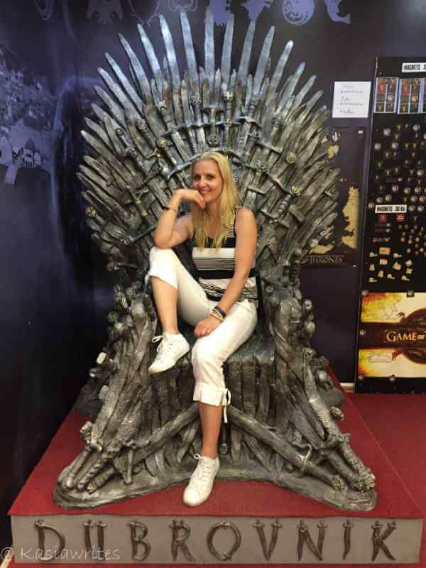 woman sitting in a throne chair made out fo swords