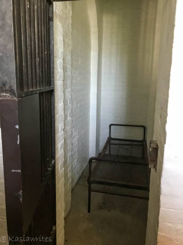 narrow prison cell with bed