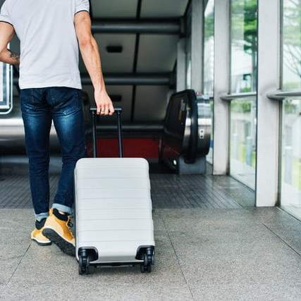 future of travel: man rolling a grey carry on suitcase towards an escalator