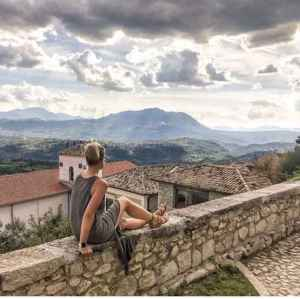 woman sitting on a wall overlooking foggy hills