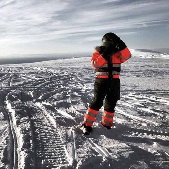 person in an orange snowmobile suite and black helmet