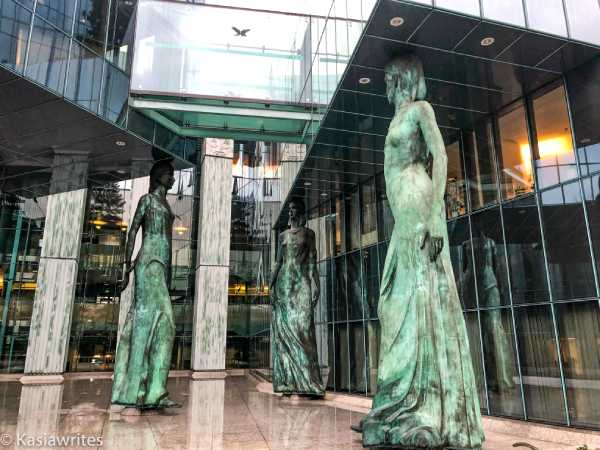 three female statues holing up glass platform with their heads