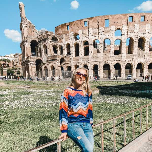 woman posing with the Colosseum in the background