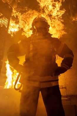 fireman standing near fire on building