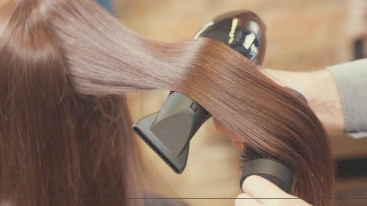 ドライヤーをかけているキレイな髪の女性画像
