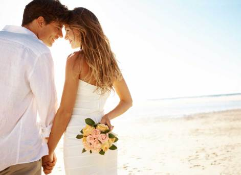 A young couple standing head-to-head on the beach while the woman holds flowers