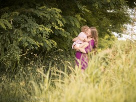 Mama tuli córeczkę wsród traw i pól.Plenerowa sesja mamy z dzieckiem z dzieckiem w Krakowie wykonana przez fotografa dziecięcego i rodzinnegp