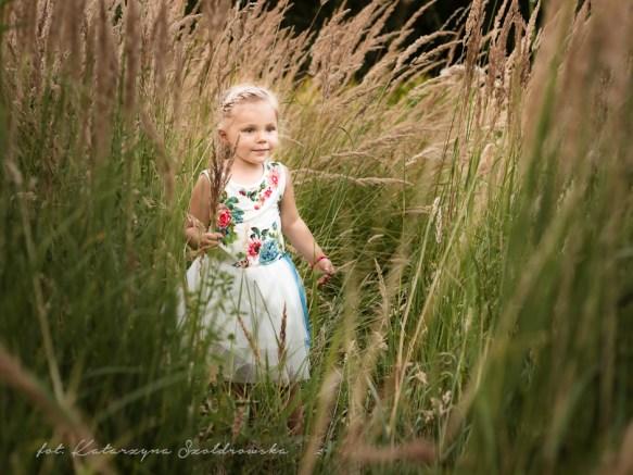 Fotografia kilkuletniego dziecka. Jasnowłosa Dziewczynka w białej sukience w kwiaty stoi pośród kwitnących traw. Sesja dziecięca wykonana w plenerze w Krakowie Mistrzejowice, Nowa Huta