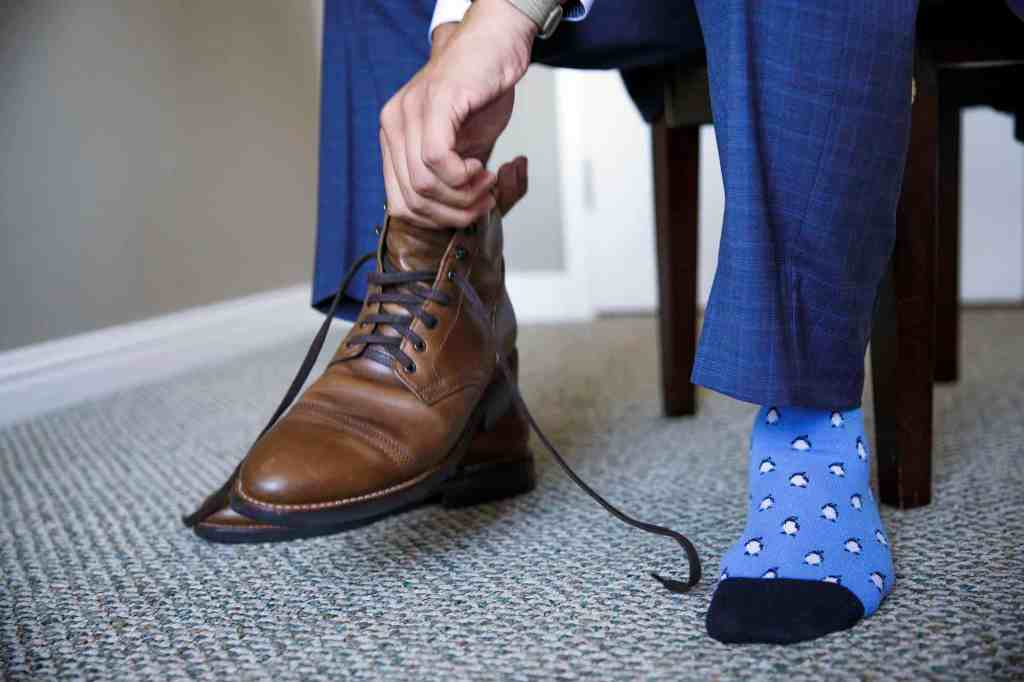 Groom putting on shoes with penguins on his socks