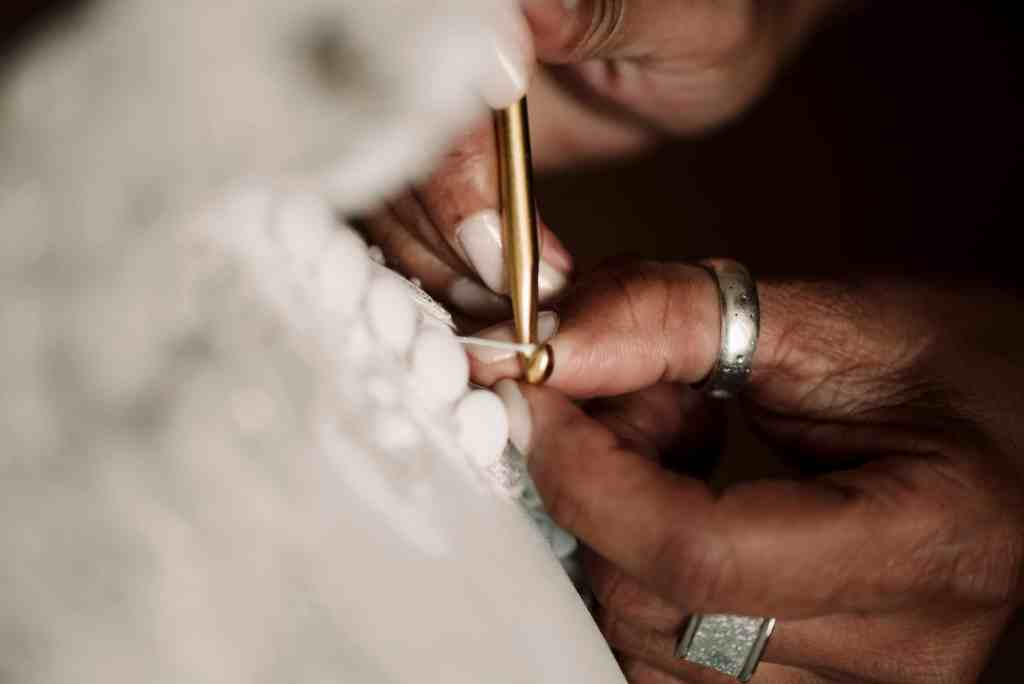 detail of wedding dress being fastened