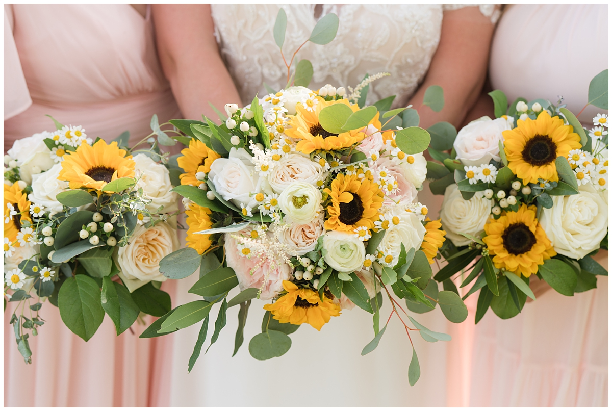 bride and bridesmaids hold bouquets with sunflowers and pink and ivory flowers