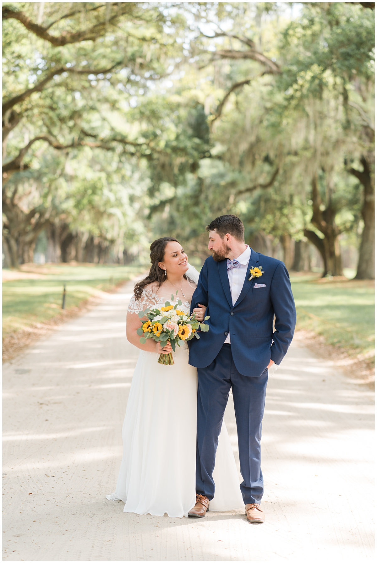 bride and groom walk through driveway of Boone Hall