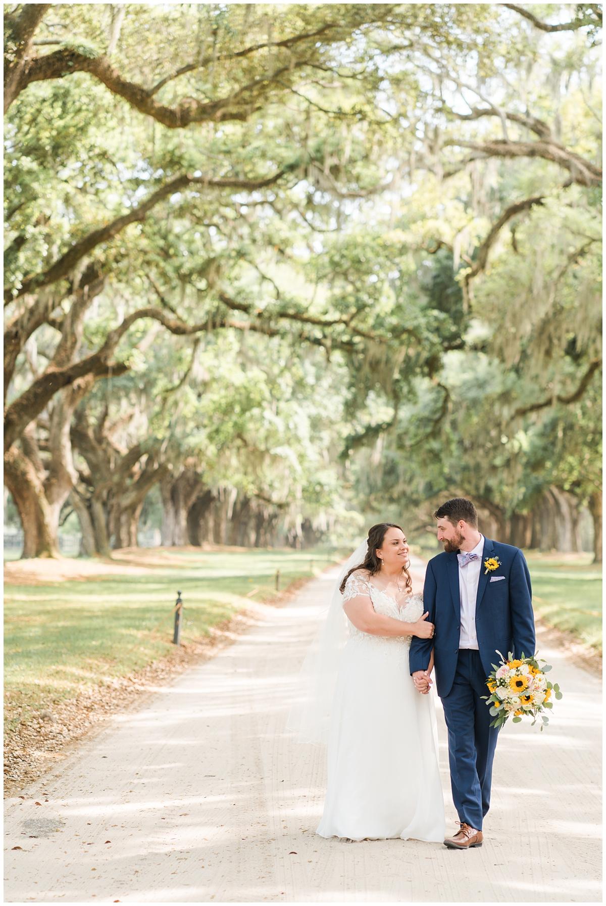 newlyweds walk outside Boone Hall during spring wedding photos