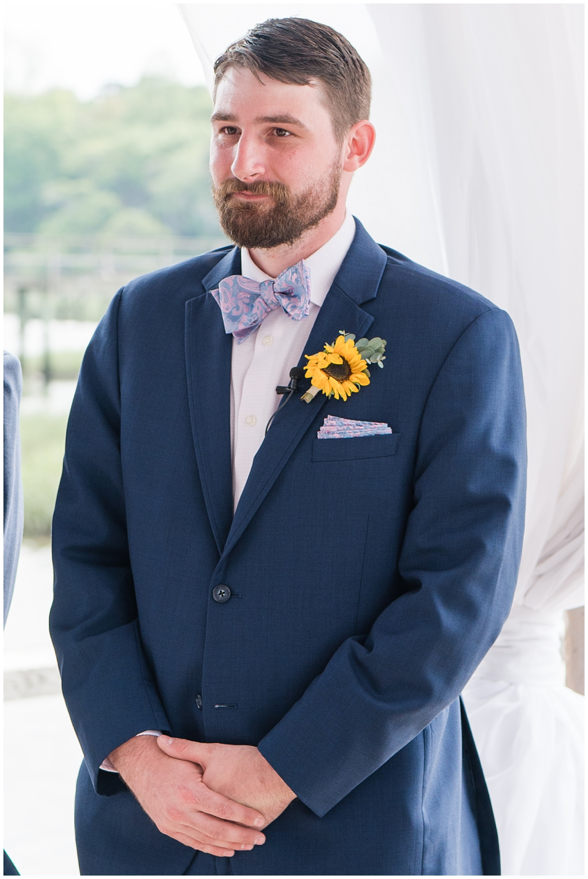 groom stands under canopy on Cotton Dock at Boone Hall
