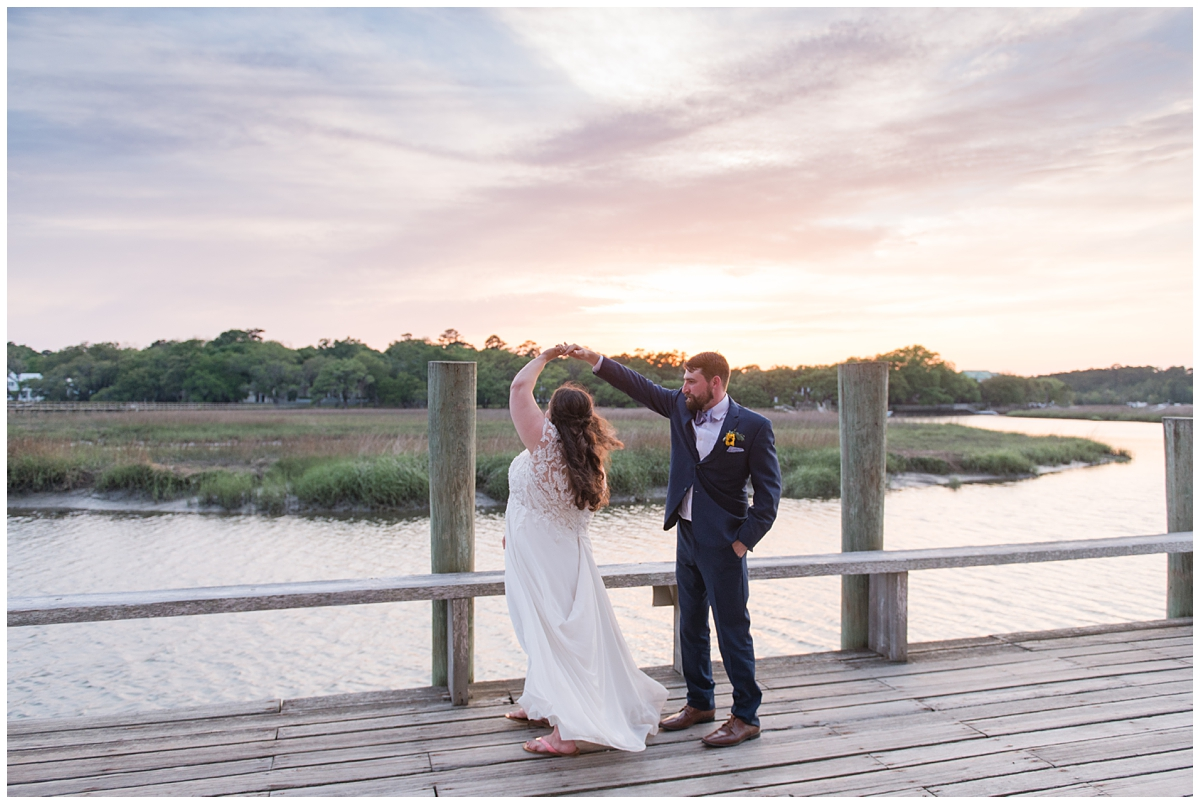 groom twirls bride on Cotton Dock at sunset at Boone Hall