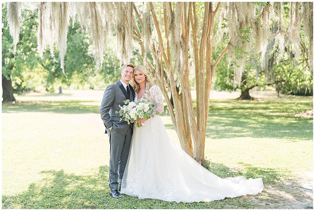 newlyweds pose by tree in Charleston SC
