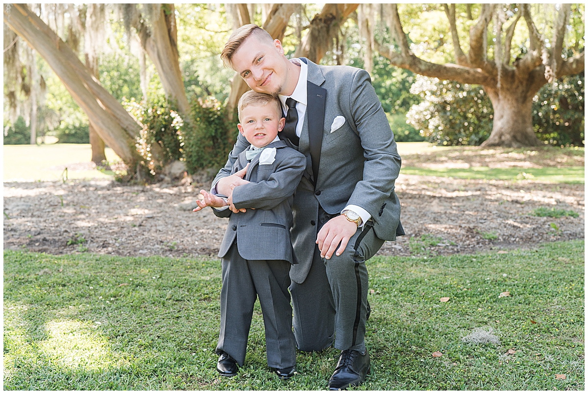 groom poses with ring bearer in Charleston SC