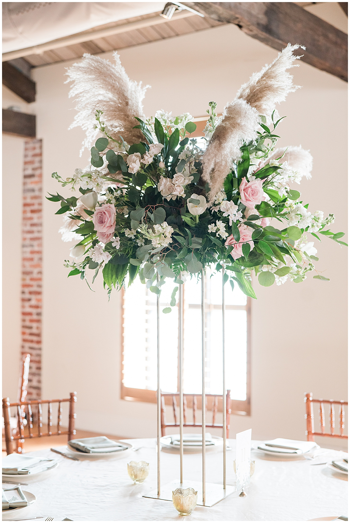 tall centerpiece for Cannon Green wedding reception with feathers and pink flowers