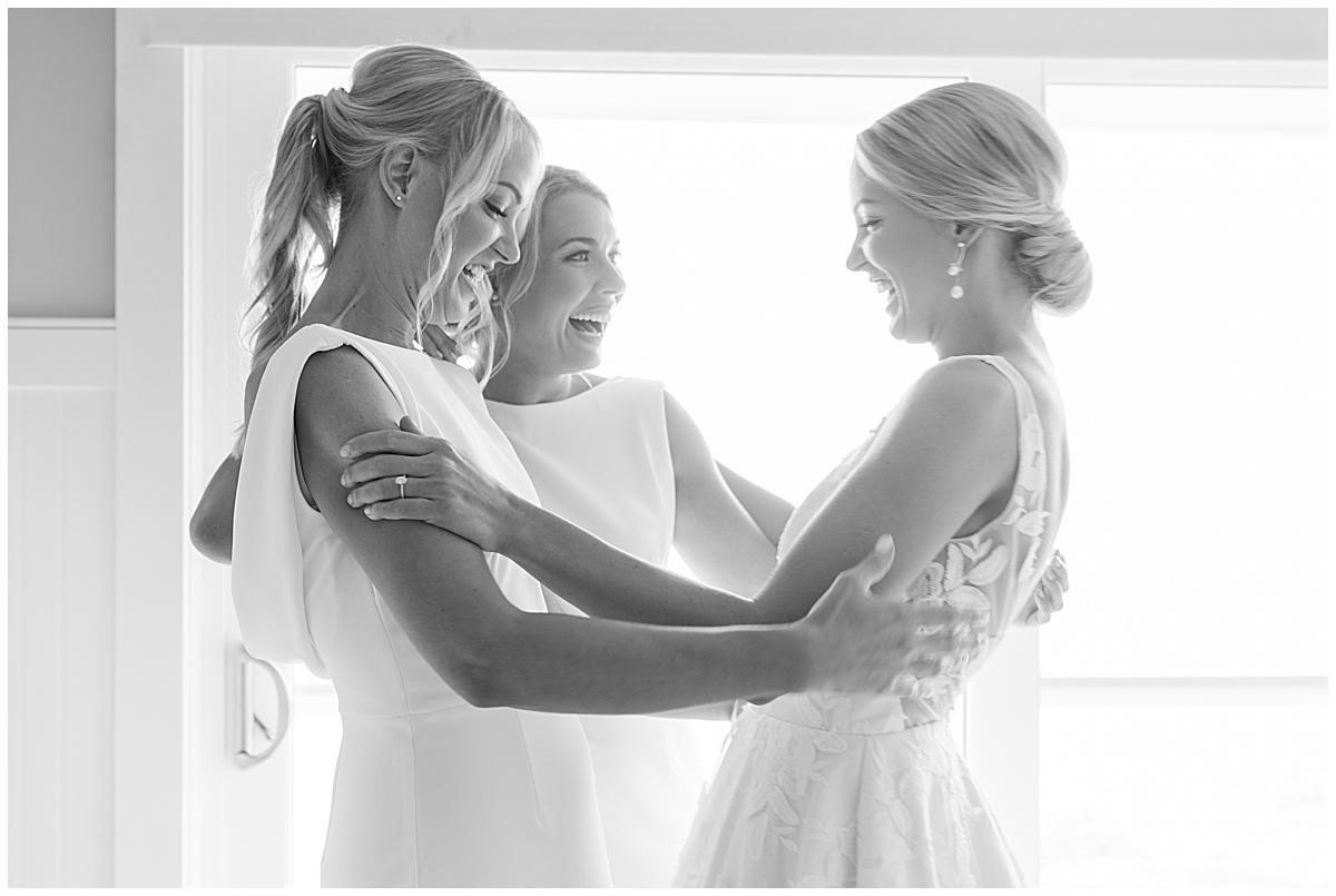 sisters hug bride before getting ready