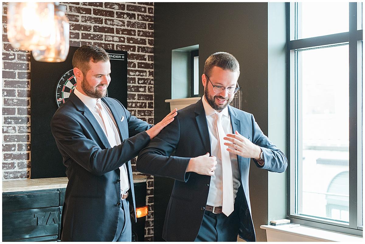 groomsman helps groom prepare for wedding at Haberdash Charleston