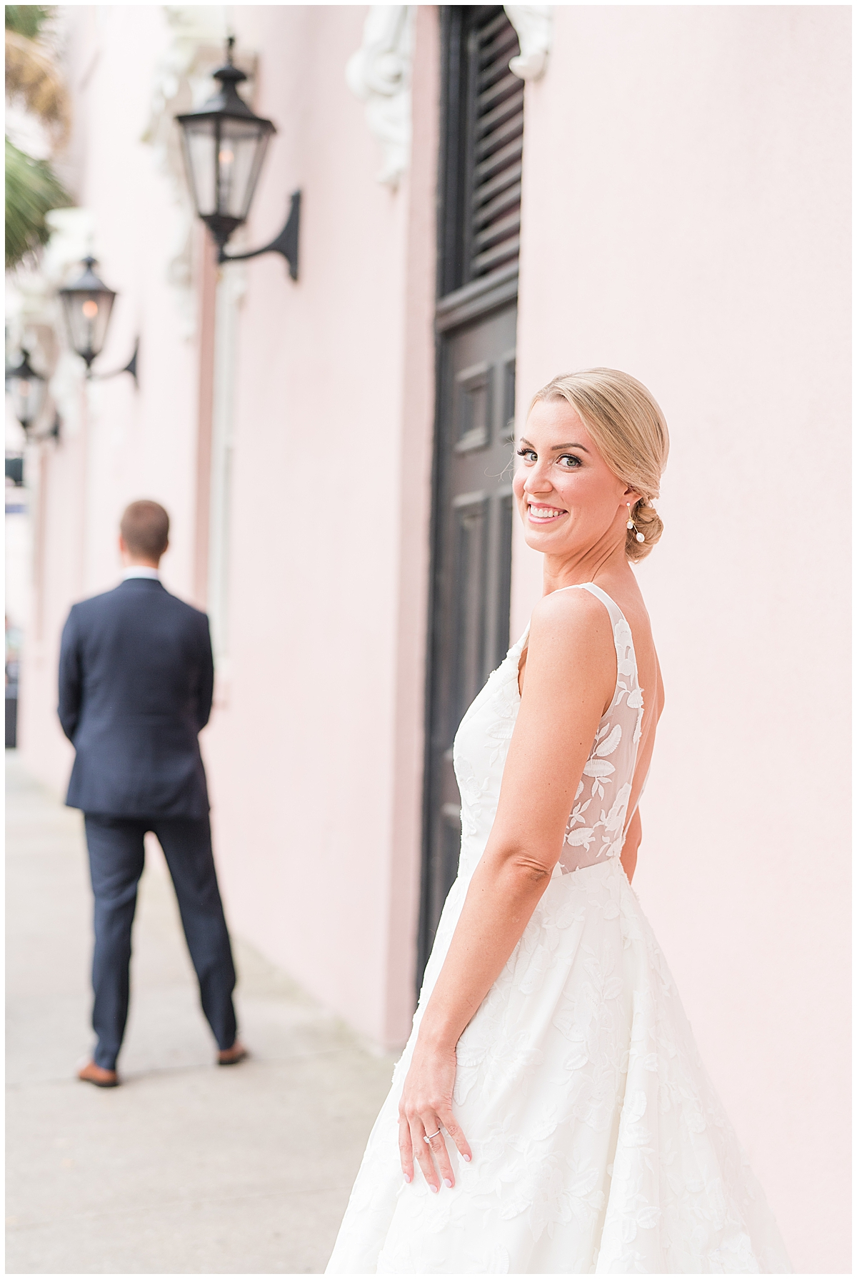 bride approaches groom along Rainbow Row in Charleston for first look
