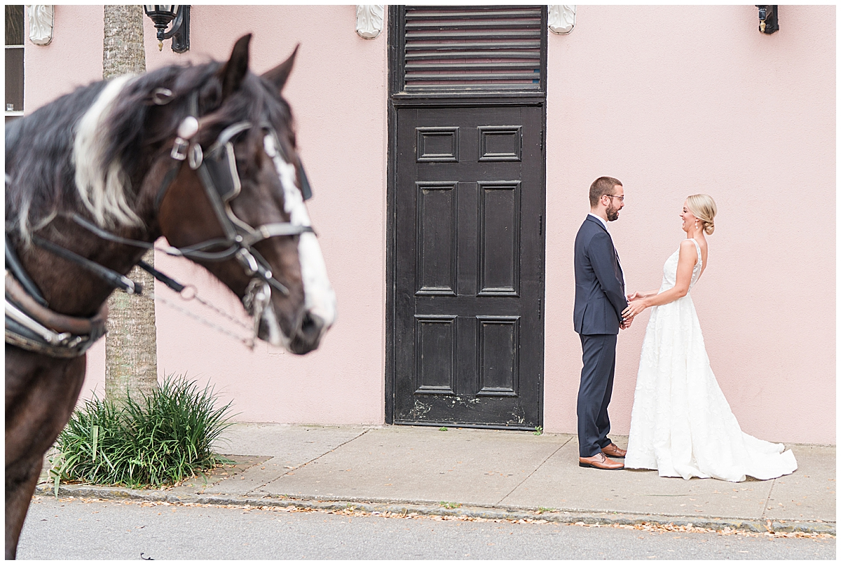 bride and groom hug during first look while horse walks by