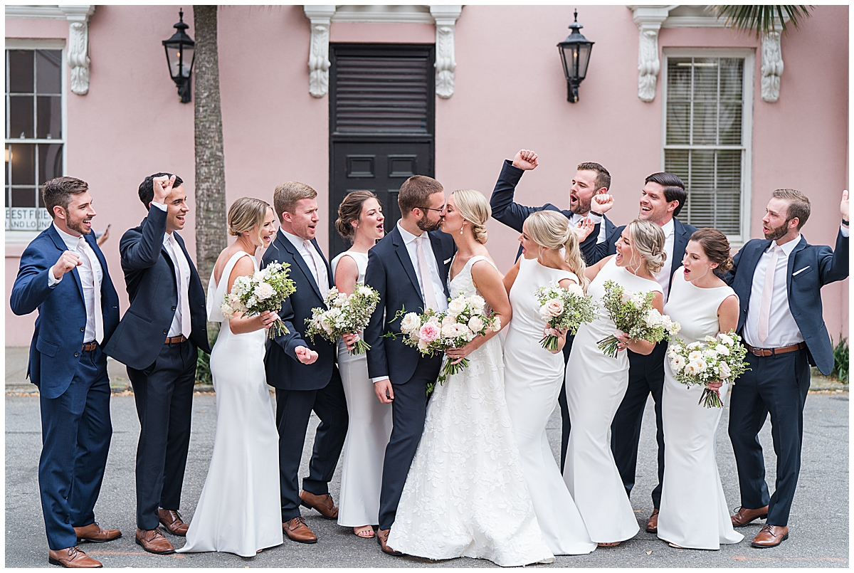 wedding party cheers while bride and groom kiss