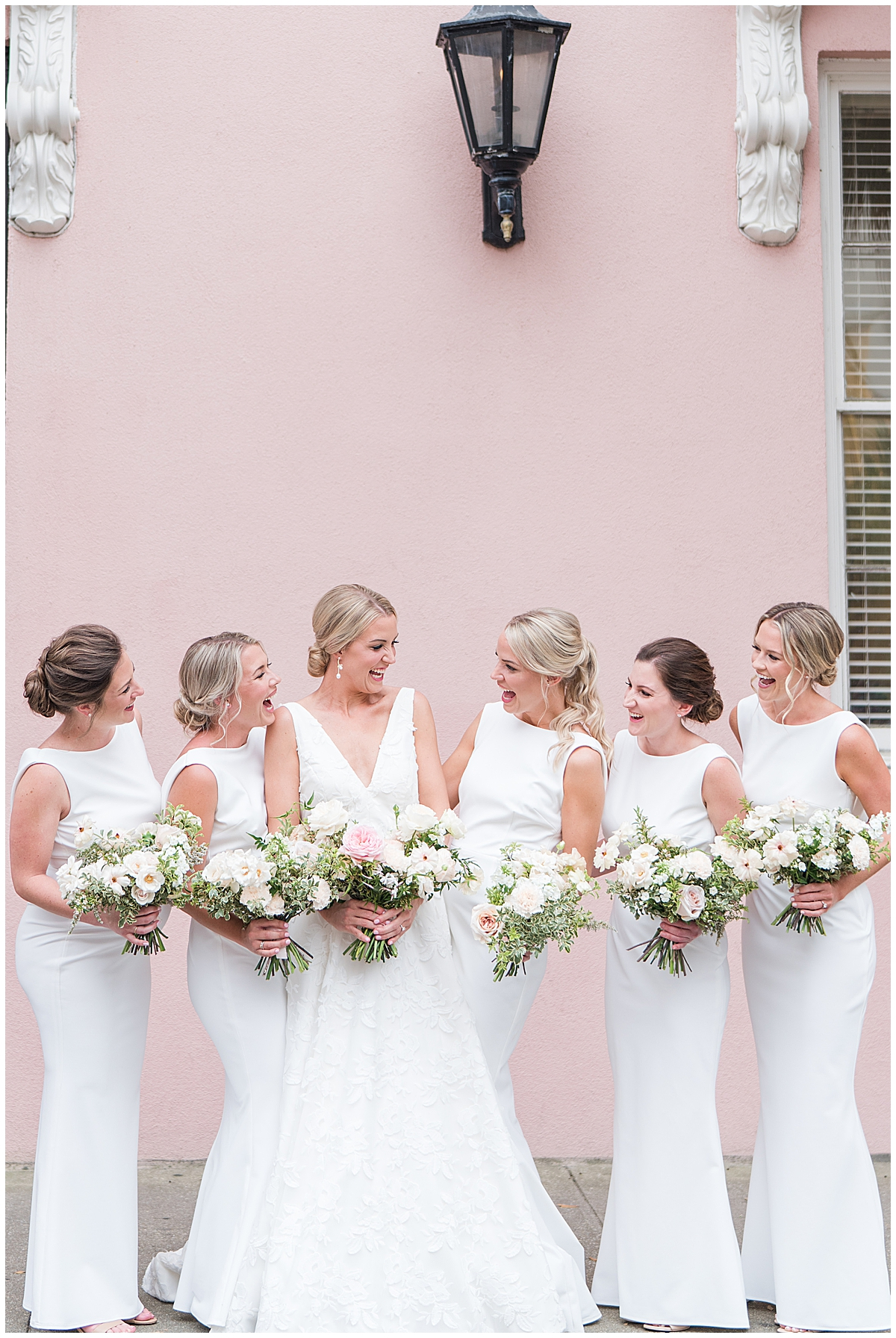 bridesmaids in white gowns smile at bride