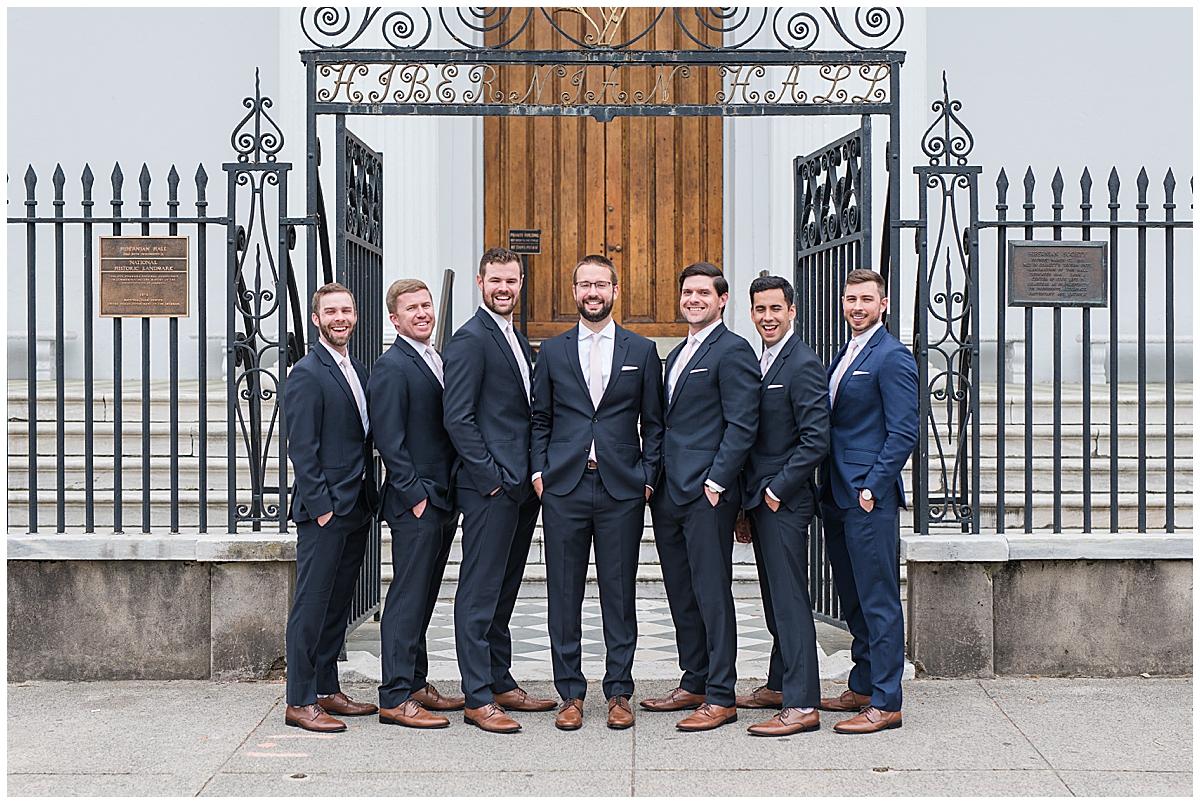 groomsmen pose by wrought iron gate in Charleston SC