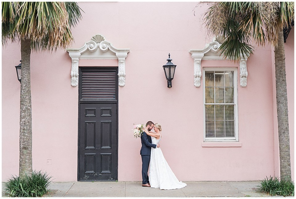 bride and groom hug by pink house on Rainbow Row