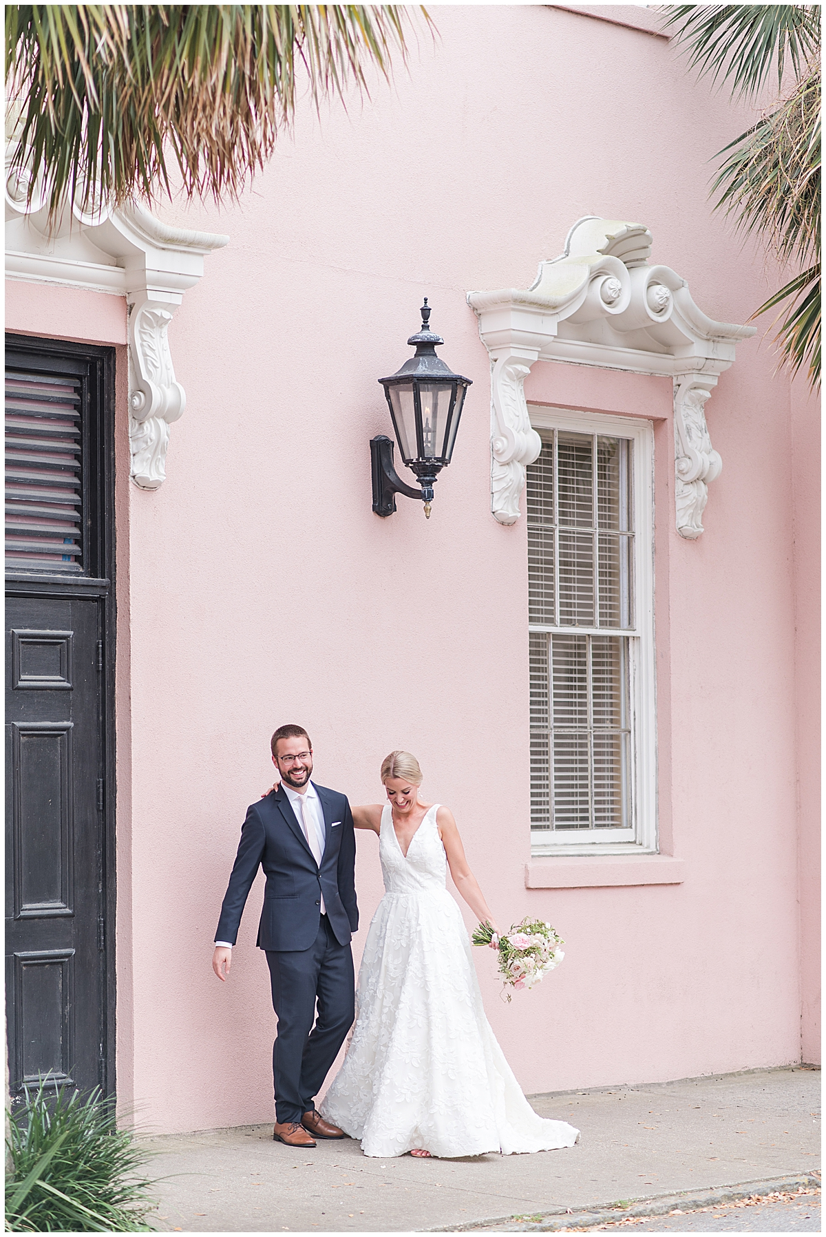 bride and groom walk by pink house on Rainbow Row