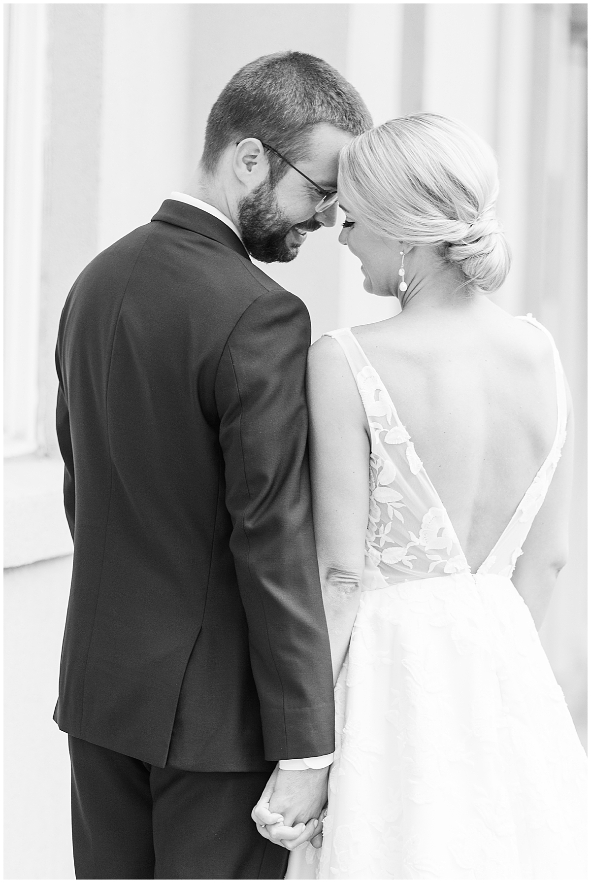bride and groom lean heads together in Charleston SC