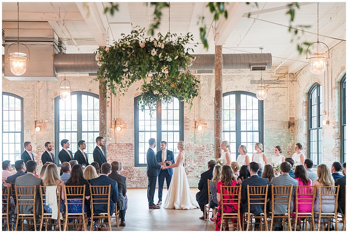 bride and groom exchange vows under hanging greenery display at Cedar Room