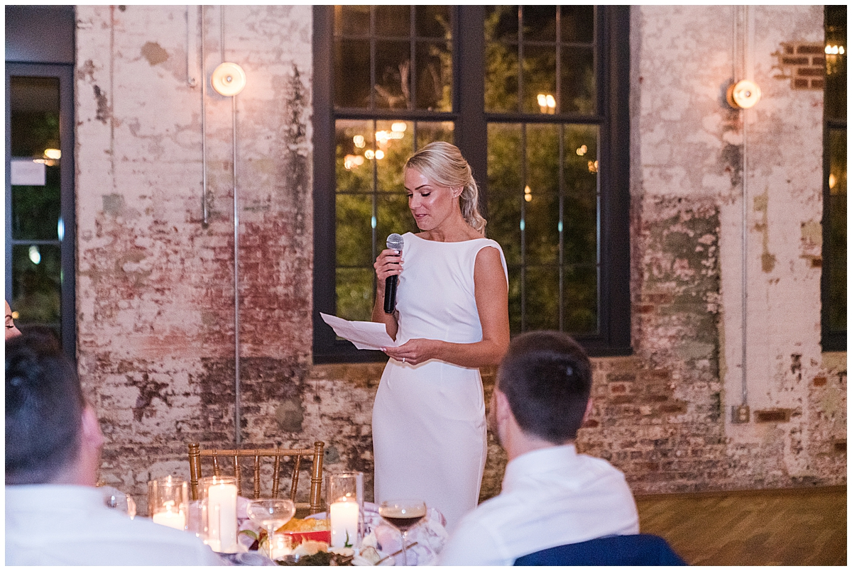 maid of honor in white dress reads speech