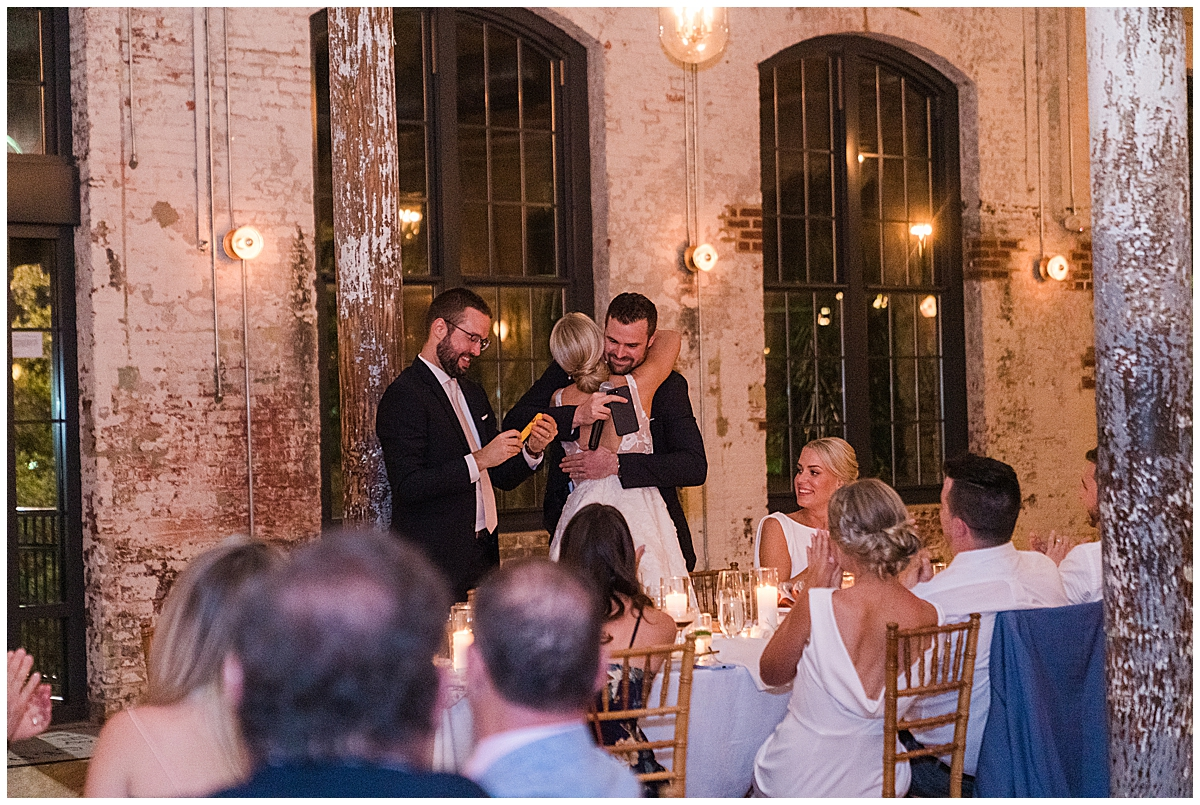 bride hugs best man during Cedar Room Charleston wedding reception