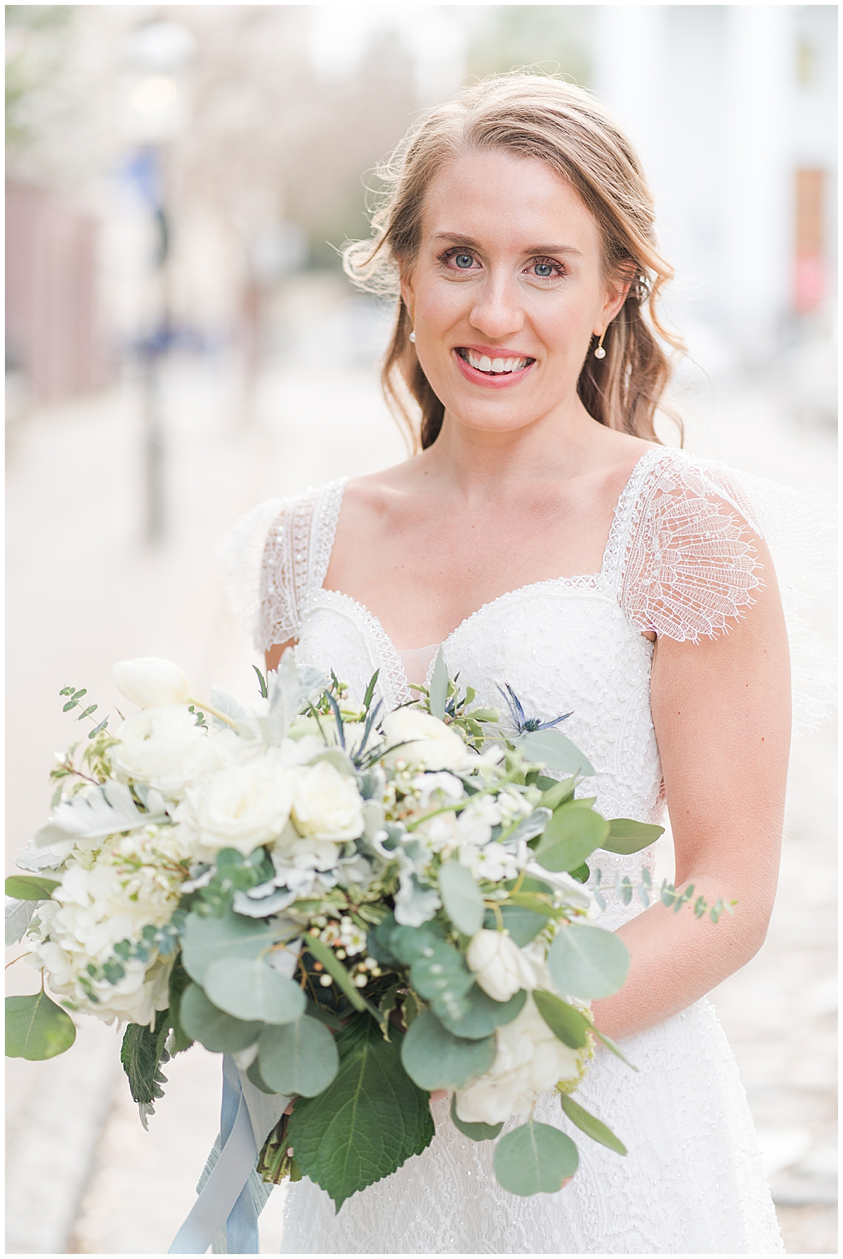 bride with cap sleeved wedding dress holds bouquet of white flowers